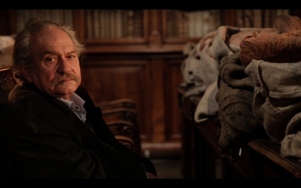 "Frame grab from the actual promo footage showing Jannis Kounellis sitting in between the library desks on which he had placed his ""Sacks of Bread""."